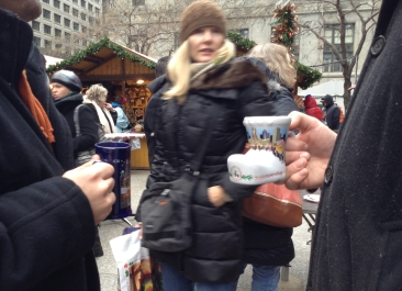 "Nov. 26, 2013, Chicago – Nick Dibona brought his 2012 boot-shaped mug to the Christkindlmarket in Daley Plaza instead of conforming to the newly designed skinny souvenir mug. ""At first I was a little skeptical because I love the boot, but now that I see them up close they're not bad,"" he says. (Alix Hines/Medill)"