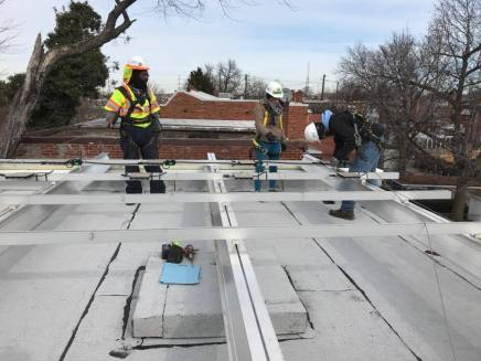 GRID Alternatives is working to install solar panels on the roof of a home in DC. (Alix Hines/CIRCA)