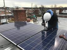 Dave from GRID Alternatives secures a solar panel on the roof of a home near the Anacostia River. (Alix Hines/CIRCA)